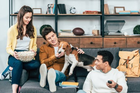 Photo for Three smiling multiethnic friends with dog and popcorn sitting on sofa and watching tv - Royalty Free Image
