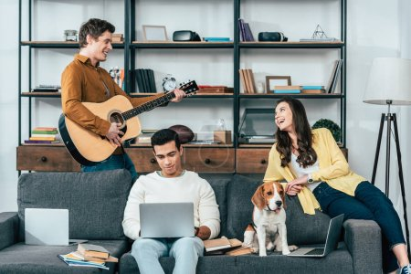 Foto de Three multicultural students with dog using laptops and playing guitar in living room - Imagen libre de derechos