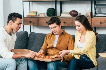 Photo for Three joyful multiethnic friends sitting on sofa and eating pizza together - Royalty Free Image
