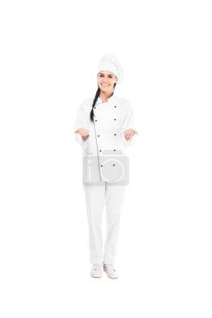Photo pour Chef souriant au chapeau montrant un geste d'haussement d'épaules isolé sur blanc - image libre de droit