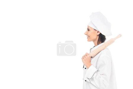 Photo pour Vue latérale du chef au chapeau tenant le rouleau à pâtisserie isolé sur blanc - image libre de droit