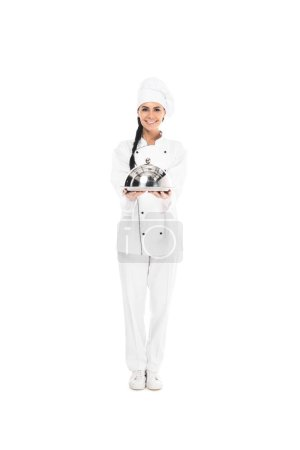 Photo for Full length of chef in hat holding tray with cloche isolated on white - Royalty Free Image