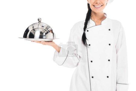 Photo pour Recadrée vue du chef en tenue uniforme plateau avec cloche isolé sur blanc - image libre de droit