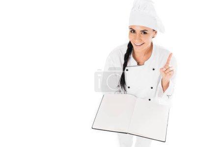 Photo pour Chef souriant tenant livre ouvert et montrant geste d'idée isolé sur blanc - image libre de droit