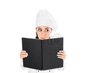 Photo pour Curieux chef en uniforme tenant livre noir isolé sur blanc - image libre de droit