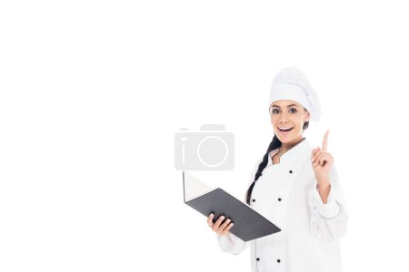 Photo for Amazed chef in uniform holding black book and showing idea gesture isolated on white - Royalty Free Image