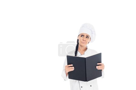 Sad chef in uniform holding black book isolated on white