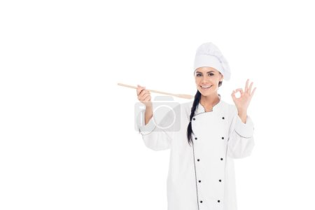 Photo for Smiling chef in uniform holding wooden spatula and showing okay sign isolated on white - Royalty Free Image