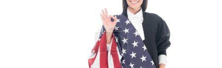 Photo pour Prise de vue panoramique du sourire juge tenant le drapeau américain et montrer signe OK isolé sur blanc - image libre de droit