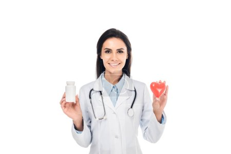 Photo for Doctor in white coat with stethoscope holding pills and plastic heart isolated on white - Royalty Free Image