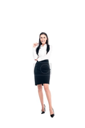 Photo for Full length view of dreamy businesswoman in black skirt holding glasses isolated on white - Royalty Free Image