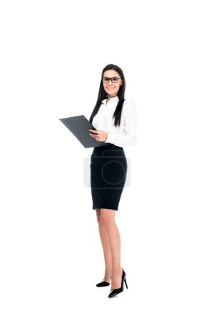 Photo for Full length view of smiling businesswoman in black skirt holding clipboard isolated on white - Royalty Free Image