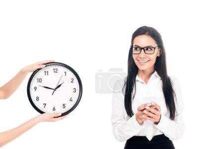 Photo pour Sourire de femme d'affaires dans des verres debout près d'horloge isolé sur blanc - image libre de droit