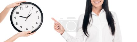 Photo for Panoramic shot of smiling businesswoman in glasses pointing with finger at clock isolated on white - Royalty Free Image