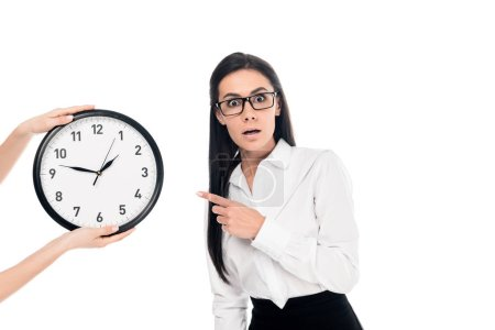 Photo for Shocked businesswoman in glasses pointing with finger at clock isolated on white - Royalty Free Image