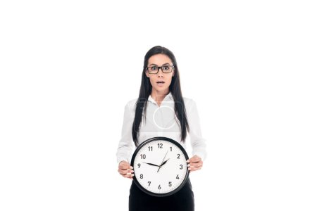 Photo for Shocked brunette businesswoman in shirt holding clock isolated on white - Royalty Free Image