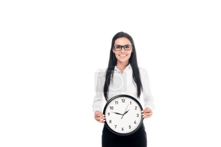 Photo for Happy brunette businesswoman in shirt holding clock isolated on white - Royalty Free Image