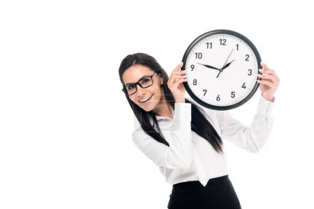 Photo for Smiling brunette businesswoman in shirt holding clock isolated on white - Royalty Free Image
