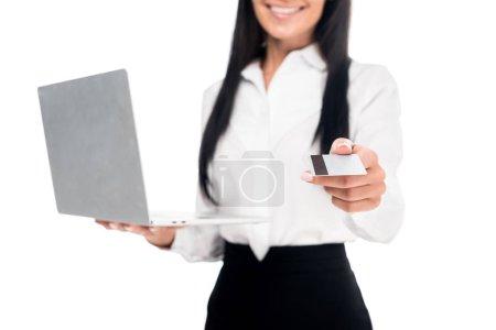 Photo pour Vue recadrée de femme d'affaires élégante dans des lunettes tenant ordinateur portable et carte de crédit isolé sur blanc - image libre de droit