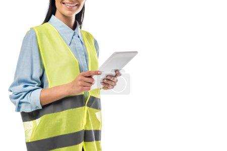 Photo pour Vue recadrée d'ingenieur en gilet de sécurité à l'aide de tablette numérique isolé sur blanc - image libre de droit