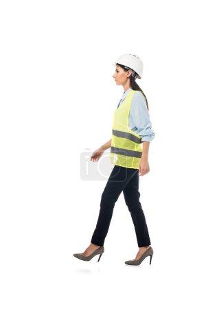 Photo pour Vue latérale de l'ingénieur dans le gilet de sécurité et les chaussures à talons hauts marchant d'isolement sur le blanc - image libre de droit