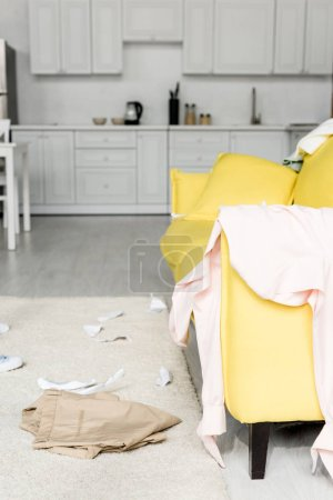 Photo for Carpet and bright yellow sofa with cloths and papers - Royalty Free Image