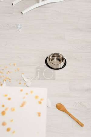 Photo for Selective focus of metal bowl, wooden spoon and broken dishes on floor in kitchen - Royalty Free Image