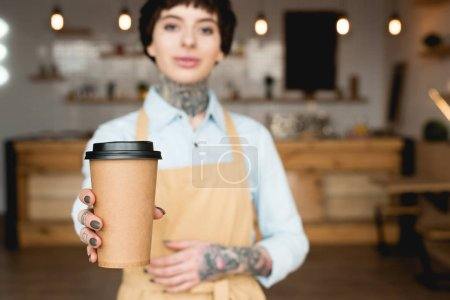 Photo for Selective focus of attractive waitress in apron holding paper cup and looking at camera - Royalty Free Image