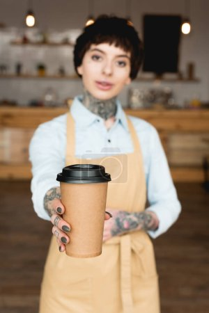 Photo for Selective focus of beautiful waitress in apron holding paper cup and looking at camera - Royalty Free Image