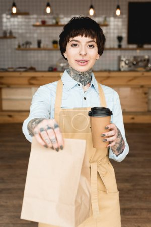 Photo for Selective focus of smiling waitress holding paper bag and disposable cup and looking at camera - Royalty Free Image
