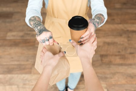 Photo for Cropped view of tattooed waitress giving paper bag and disposable cup to customer - Royalty Free Image