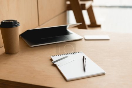 Photo for Selective focus of woode table with laptop, paper cup, notebook and credit card in cafe - Royalty Free Image