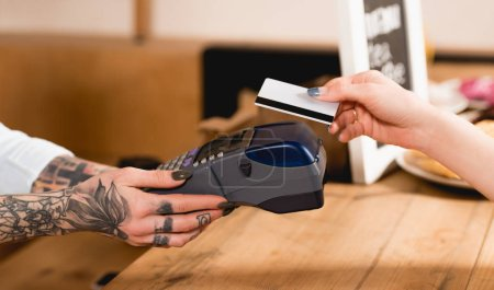 Photo for Cropped view of customer holding credit card near payment terminal in cafe - Royalty Free Image