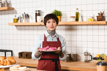 Photo pour Jolie barista tenant plat avec des biscuits délicieux et en regardant la caméra - image libre de droit
