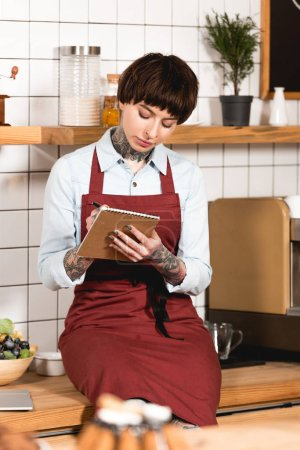 Photo for Beautiful concentrated barista in apron writing in notebook - Royalty Free Image