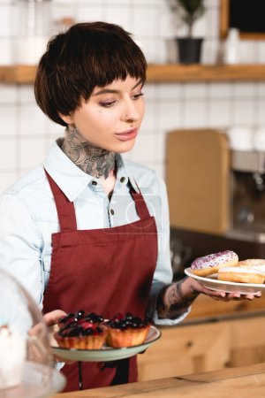 beautiful barista holding plates with delicious pastry in coffee shop