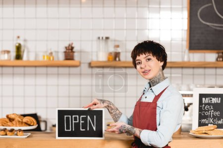 Photo for Smiling barista holding signboard with open inscription and looking at camera - Royalty Free Image