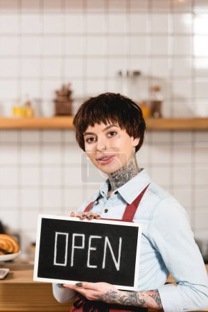 Photo for Beautiful barista holding signboard with open inscription and looking at camera - Royalty Free Image
