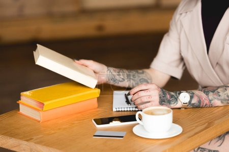 Photo for Partial view of businesswoman sitting at table with books, smartphone and coffee cup - Royalty Free Image