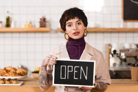 Photo pour Jolie femme d'affaires tenant enseigne avec lettrage ouvert et regardant la caméra - image libre de droit