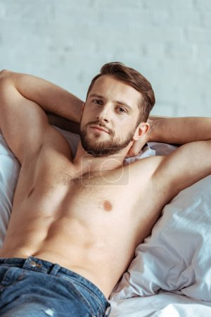 Photo for Good-looking and muscular man lying on bed and looking at camera in bedroom - Royalty Free Image