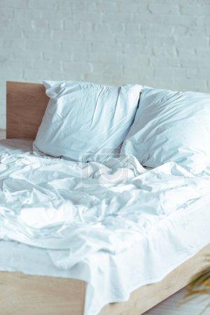 Foto de Madera y acogedora cama con almohadas, manta, hoja en dormitorio - Imagen libre de derechos