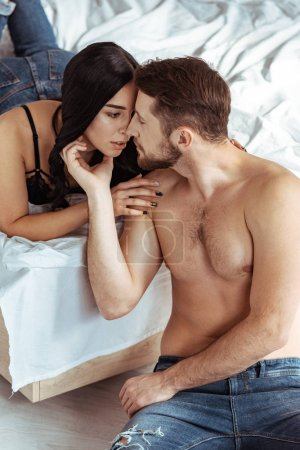 Photo pour Beau, musclé et torse nu homme étreignant avec belle femme en soutien-gorge en dentelle - image libre de droit