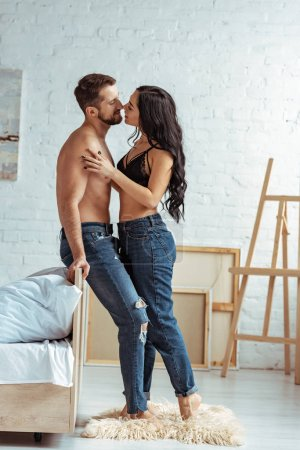 Photo for Handsome and muscular man hugging with beautiful and smiling woman in lace bra in bedroom - Royalty Free Image