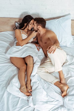 Photo for Attractive woman lying in bed and hugging with handsome man in bedroom - Royalty Free Image