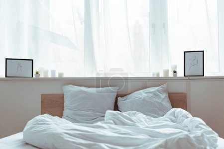 Photo for Modern bedroom with cozy bed, pillows, blanket, pictures in daytime - Royalty Free Image