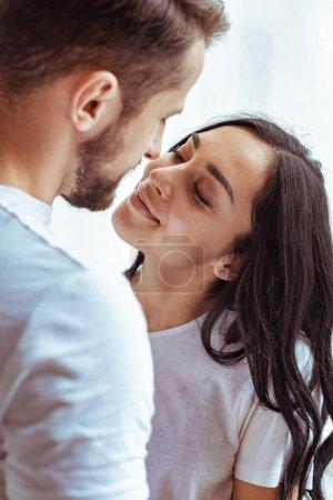 Photo pour Bel homme et belle femme en t-shirt se regardant et s'embrassant - image libre de droit