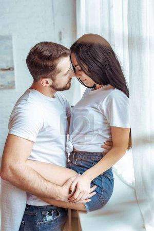 Photo pour Bel homme embrassant belle femme brune en t-shirt et short - image libre de droit