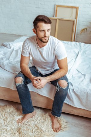 Photo for Good-looking man in white t-shirt and jeans looking away - Royalty Free Image