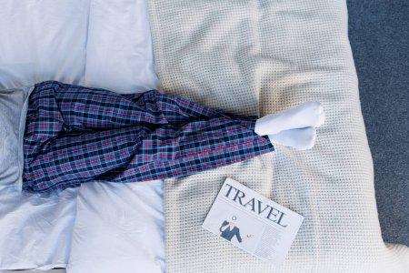 Photo pour Vue partielle de l'homme en pyjama couché sur le lit près d'un journal de voyage - image libre de droit